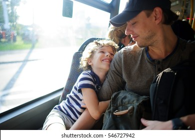 The young man goes by the bus together with the son. The father and the son sit next with each other and communicate with pleasure. On their faces expression of love and joy.