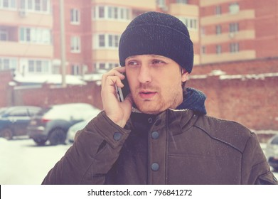 Young man with goes on the winter city and speaks by phone.
