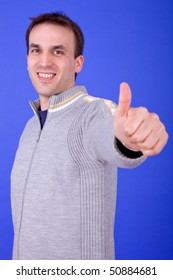 an young man going thumb up over a blue background