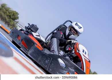 young man go-kart racer is racing a race in an outdoor go karting circuit - focus on the left eye