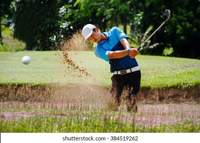 young man golf player in Blue shirt in action swing his sand wedges in sand pit explode sand and golf ball diffusing in the air