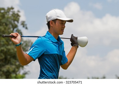 young man golf player exercise by put driver on shoulder to warm up before play golf under bright sky
