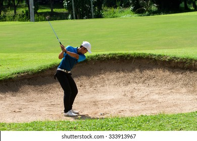 young man golf player hit ball in sandpit under sunlight in golf practice