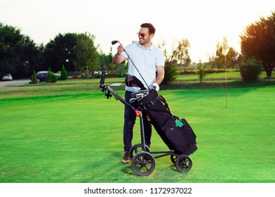 Young man golfer taking out the golf club from a bag
