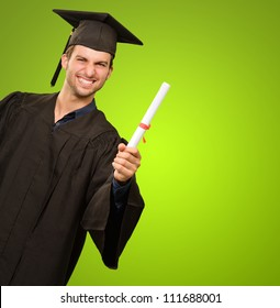 Young Man In Graduation Gown Holding Certificate On Green Background