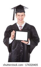 Young Man In Graduation Robe Showing Blank Tablet Pc Over White Background