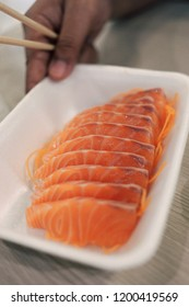 A young man grap a fresh salmon slice with chopstick