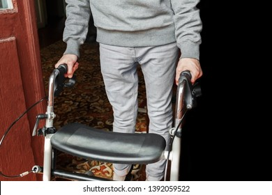 young man in gray clothes is standing with a walker on the floor in his room. rehabilitation of victims in hostilities after injuries concept. problem of war victims and disabled veterans