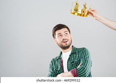 Young man in green checked T-shirt and crown above his head. Looking at crown, surprised. Waist up, hands crossed. Indoors, studio