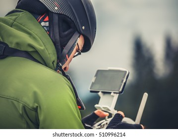 Young man in green jacket operating a drone using a remote controller. Blue sky in the background, winter holidays in mountains. Bukovel, Carpathians, Ukraine, Europe. Exploring beauty world