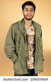 Young Man in green military Jacket on beige Background