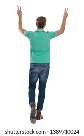 young man in green polo shirt walking back with hands up showing V sign on white background