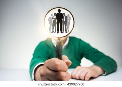 Young man in green pullover with people icons inside magnifier instead of head on light background. Concept of HR management