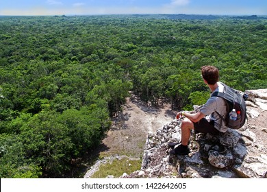 A young man with a grey backpack sitting on the top of the famous pyramid of Coba, Yucatan, Mexico. The jungle in the background reaches till the horizon. Concept of travel, nature and ancient culture