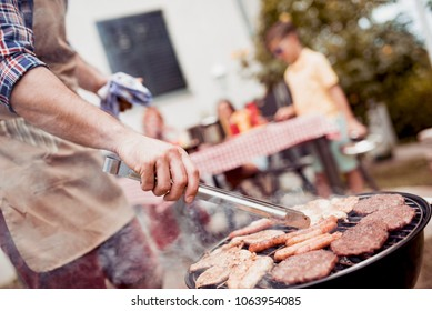 Young man grilling meat on barbecue for family dinner in the backyard of the house.