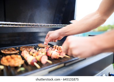 Young man grills some kind of marinated meat and vegetable on gas grill during summer time