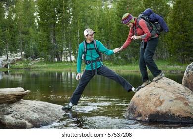 A young man grips the hand of his girlfriend as he helps her across a mountain stream.