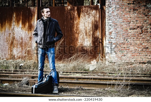 Young man with guitar case waiting for the train among industrial ruins
