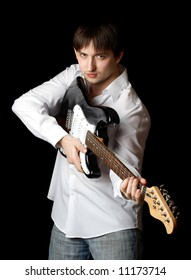 Young man with guitar isolated on black