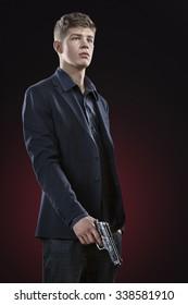 Young man with gun. Dark red background. Standing portrait.