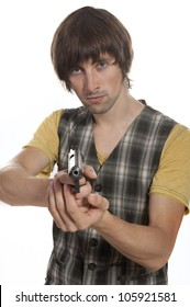 A young man with a gun in his hand on a white background in the studio