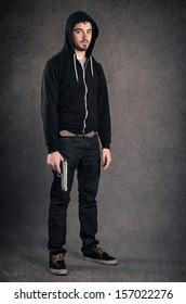 Young man with gun portrait over dark grunge background. Full body.