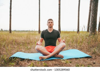Young man guy sitting on a rug in the lotus position. Practicing yoga in asana position. The concept of a healthy lifestyle or hobby. Reach nirvana, without stress. Summer forest.