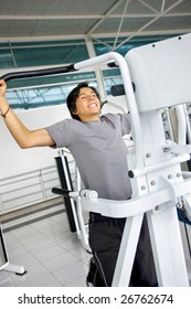 Young man at the gym doing chin ups
