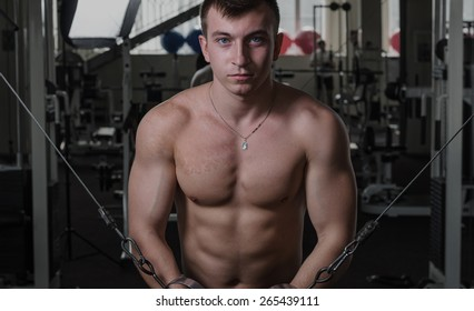 Young man at the gym exercise on the pectoral muscles, the reduction in the hands of crossover