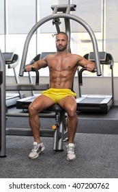 Young Man In Gym Exercising On Machine Chest Press