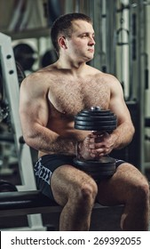 A young man in the gym performing an exercise one-arm dumbbell curl. Toning, hard light.