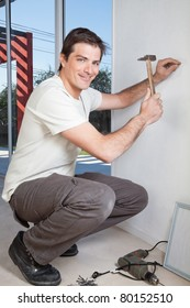 Young man with hammer nailing the wall