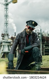 Young man with hammer weared in steampunk style working on railway near by factory