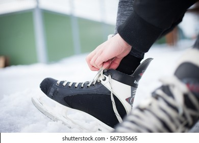 Young man hand commits laces on ice skates and prepare for ice skating