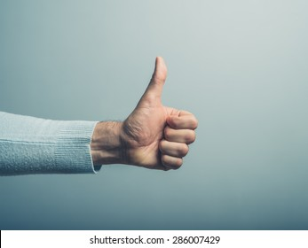 A young man' hand is displaying a thumbs up, indicating that he likes or approves of something