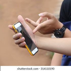 young man hand hold phone, young adult using mobile smart phone, Internet of things lifestyle with wireless communication and internet with smartphone. Travel and internet outdoor,