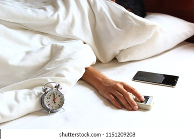 Young man hand hold remote air conditioner and sleeping in the bedroom at home