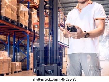Young man hand holding a barcode scanner checking and inventory a goods in warehouse factory