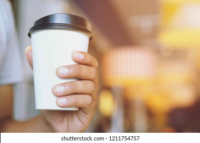 young man hand holding Paper cup of take away drinking coffee hot on cafe coffee shop.