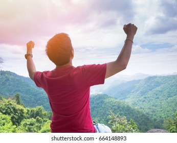 Young man hand up with the nature background - Asian male successful freedom lifestyle outdoor at the mountain landscape, Thailand