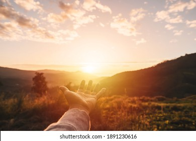 Young man hand reaching for the mountains during sunset and beautiful landscape
