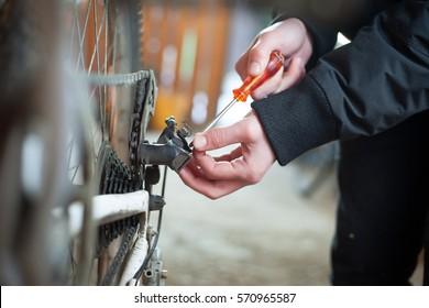 Young man hand repairing his professional bike for another season in garage, preparing