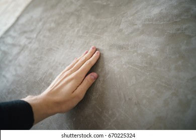 young man hand touching concrete wall