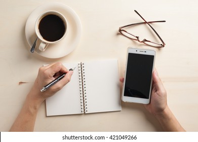 Young man hand writing on blank notebook while another hand holding smartphone on wood table with coffee cup and glasses beside in morning time