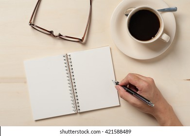 Young man hand writing on blank notebook on wood table with coffee cup and glasses beside in morning time