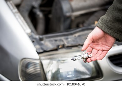 Young man hands changing car bulb / headlight, repairing car