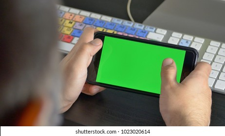 Young Man Hands Holding A Smartphone With Green Screen
