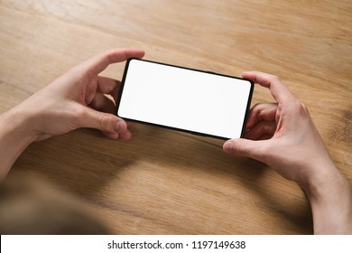 young man hands holding smartphone with blank white screen in landscape mode