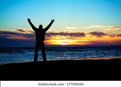 young man hands up on a beach at sunset