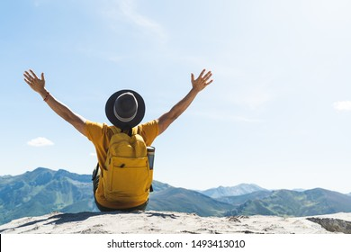 Young Man Hands Up Sitting on Top of a Mountain Wearing a Yellow Backpack. Young Guy Raising Hands Up in the Nature. Indian Man in the Mountain. Lifestyle Concept.